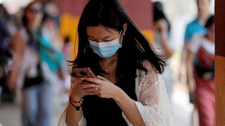 Une touriste chinoise portant un masque chirurgical, au Sri Lanka, le 28 janvier 2020. (DINUKA LIYANAWATTE / REUTERS)