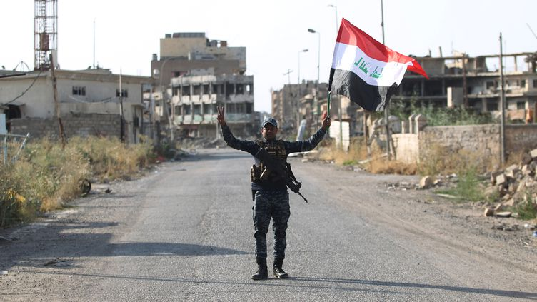 Un policier irakien brandit le drapeau de son pays, le 9 juillet 2017 dans la vieille ville de Mossoul, libérée de l'Etat islamique. (AHMAD AL-RUBAYE / AFP)