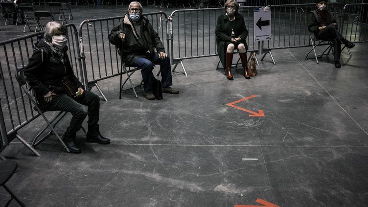Des patients attendent de se faire vacciner contre le Covid-19 au Palais des sports de Lyon, le 14 janvier 2021. (JEAN-PHILIPPE KSIAZEK / AFP)