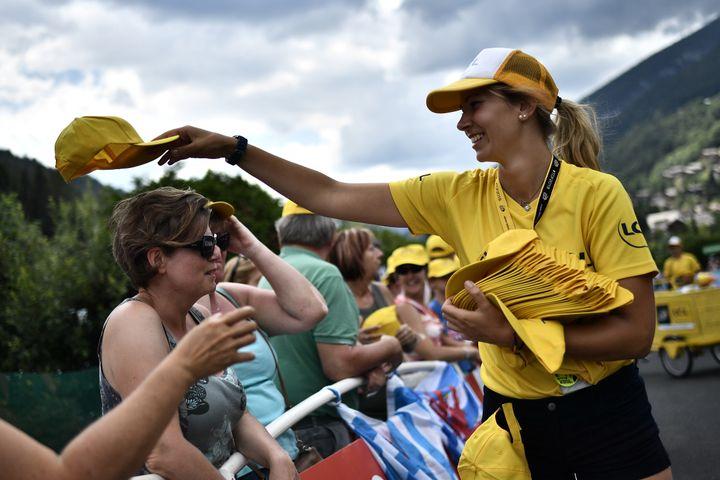 Une hôtesse distribue des casquettes au public lors de l'étape du Tour de France entreAnnecy et le Grand-Bornand (Haute-Savoie), le 17 juillet 2018. (MARCO BERTORELLO / AFP)