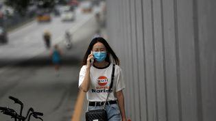Téléphone à l'oreille, une femme marche dans les rues de Pékin (Chine), le 13 juillet 2020. (TINGSHU WANG / REUTERS)