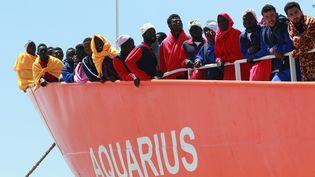 """Des migrants à bord du navire humanitaire """"Aquarius"""" arrivent dans le port de Salerne (Italie), le 26 mai 2017. (CARLO HERMANN / AFP)"""