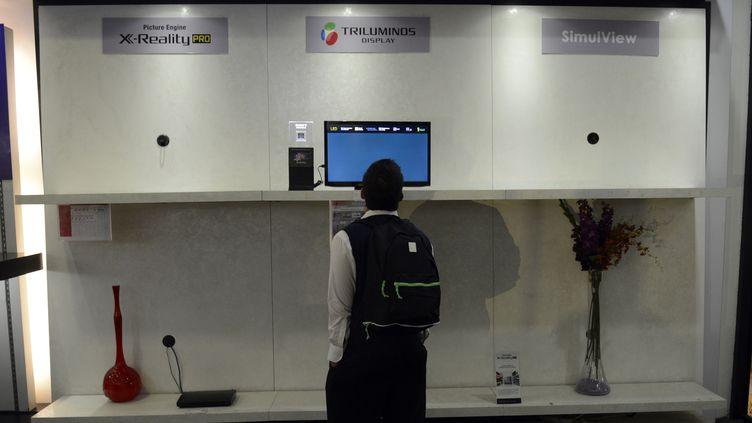 Un homme passe devant un magasin d'électronique, le 26 novembre 2013, à Caracas (Venezuela). (LEO RAMIREZ / AFP)