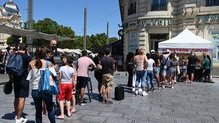 Une file d'attentepour passer un test de dépistage du Covid-19 devant une pharmacie à Montpellier (Hérault), le 9 août 2021. (PASCAL GUYOT / AFP)