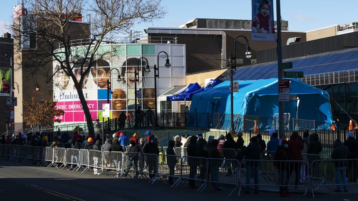 Des dizaines de personnes font la queue pour se faire tester, devant l'hôpital Elmhurst, à New York (Etats-Unis), le 24 mars 2020. (EDUARDO MUNOZ ALVAREZ / GETTY IMAGES NORTH AMERICA / AFP)