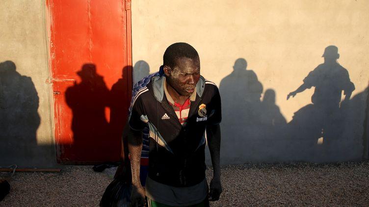 Un homme clandestin est menacé par la police libyenne à Tripoli (Libye), le 13 mars 2015. (GORAN TOMASEVIC / REUTERS)