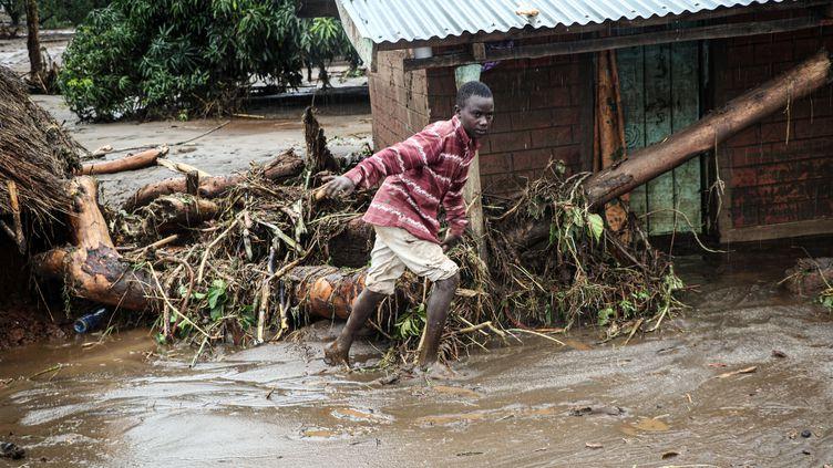 Un enfant marche dans la boue après les inondations provoquées par la rivière Muruny, le 24 novembre 2019. (STRINGER / AFP)