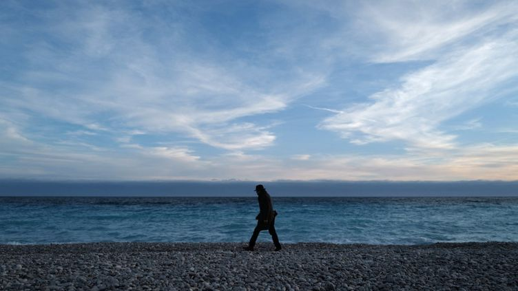 Un homme marche sur la plage déserte, à Nice, le 16 février 2021. (VALERY HACHE / AFP)