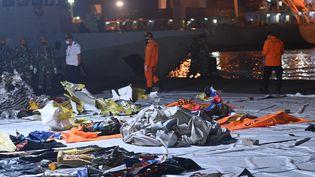Des enquêteurs indonésiens étudient, le 11 janvier 2021 à Jakarta, les débris retrouvés après le crash en mer d'un Boeing de Sriwijaya Air deux jours plus tôt. (ADEK BERRY / AFP)