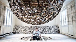 Sambre, assis sous son incroyable sphère en lattes de plancher, en suspension entre deux étages aux Bains Douches.  (Stéphane Bisseuil)