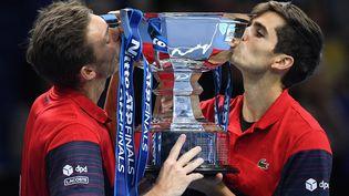 Nicolas Mahut et Pierre-Hugues Herbert posent avec leur trophée après avoir remporté leur match de finale du double masculin du tournoi de tennis ATP World Tour à l'O2 Arena de Londres, le 17 novembre 2019. (DANIEL LEAL-OLIVAS / AFP)