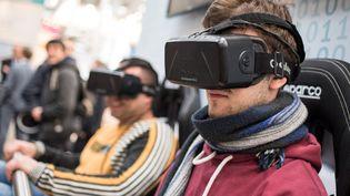 Des visiteurs du Cebit, salon pour les technologies, testent des casques de réalité virtuelle, à Hanovre (Allemagne), le 17 mars 2015. (OLE SPATA / DPA / AFP)