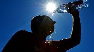 Un homme se rafraîchit à l'aide d'une bouteille d'eau en pleine canicule, le 29 juin 2015. (MAXPPP)