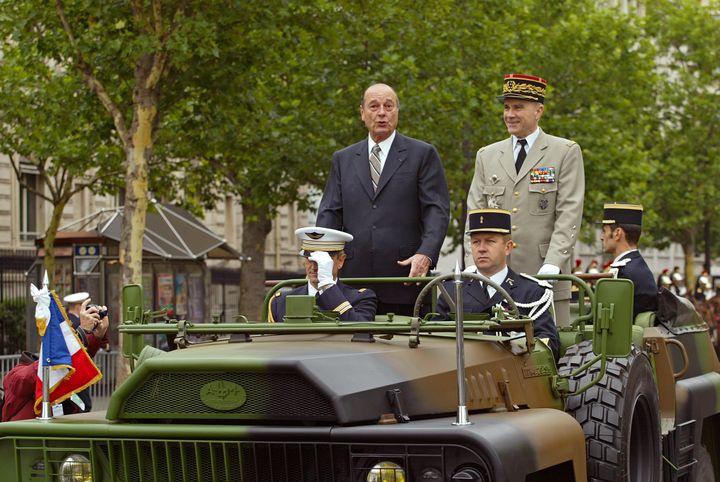 Le président de la République Jacques Chirac et le chef d'état-major des armées Jean-Pierre Kelche descendent les Champs-Elysées à bord d'un véhicule militaire, le 14 juillet 2002, à Paris, lors du traditionnel défilé militaire. (PHILIPPE DESMAZES / AFP)