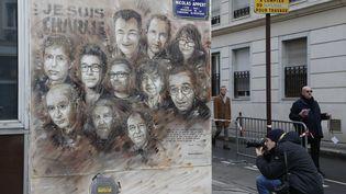 """L'oeuvre de C215 avec les visages des membres du journal satirique """"Charlie Hebdo"""" tués le 7 janvier 2015 par des terroristes, rue Nicolas Appert à Paris. (FRANCOIS GUILLOT / AFP)"""