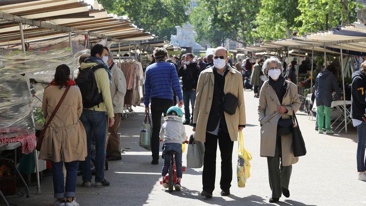Des passants portant un masque au marché avenue de Saxe à Paris, le 14 mai 2020 (LUDOVIC MARIN / AFP)