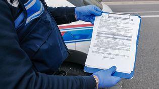 Un policier dresse un procès verbal de contravention lors d'un contrôle pendant le confinement, le 30 mars 2020, à Nice (Alpes-Maritimes). (ARI? BOTBOL / HANS LUCAS / AFP)