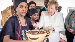 La chancelière Angela Merkel (CDU) reçoit des noix de cola et des dattes à l'aéroport de Niamey, au Niger, le 2 mai 2019. (MICHAEL KAPPELER / DPA)