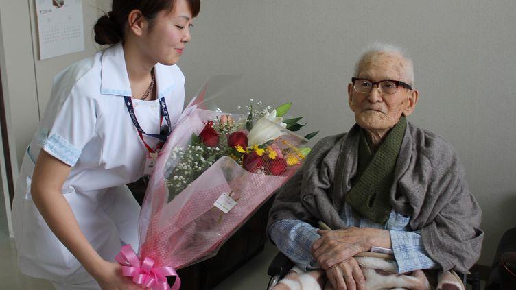Un homme de 115 ans reçoit un bouquet de fleurs, à l'hôpital deKyotango,dans la préfecture de Kyoto, au Japon, le 26 décembre 2012. (KYOTANGO CITY GOVERNMENT / AFP)