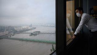 Un homme regarde la rivière Han gonflée par des fortes pluies au centre de Séoul (Corée du Sud), le 6 aout 2020. (ED JONES / AFP)