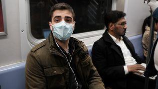 Un homme porte un masque médical dans le métro de New York alors que les Etats-Unis sont confrontés à l'épidémie de coronavirus, le 11 mars 2020. (SPENCER PLATT / AFP)