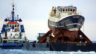"""L'épave du """"Bugaled Breizh"""" est remorquée jusqu'au port de Brest, dans le Finistère, le 13 juillet 2004. (FRED TANNEAU / AFP)"""