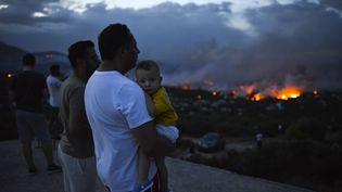 Un homme tient son fils en regardant les incendies à Rafina (Grèce), le 23 juillet 2018. (ANGELOS TZORTZINIS / AFP)