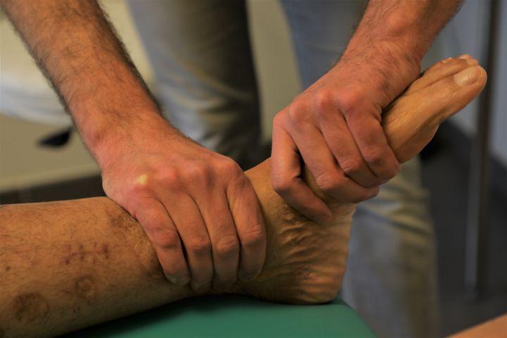Le kinésithérapeute Xavier Brocorens masse le pied de son patient Manuel Martinez, rescapé des attentats de Bruxelles en 2016, le 18 mars 2021 à Buggenhout (Belgique). (VALENTINE PASQUESOONE / FRANCEINFO)