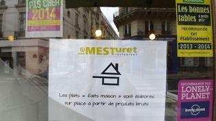 """Le label """"fait maison"""", une casserolesurmontée d'un toit de maison, apposé sur la vitrine du restaurant Le Mesturet, à Paris, le 15 juillet 2014. (MIGUEL MEDINA / AFP)"""
