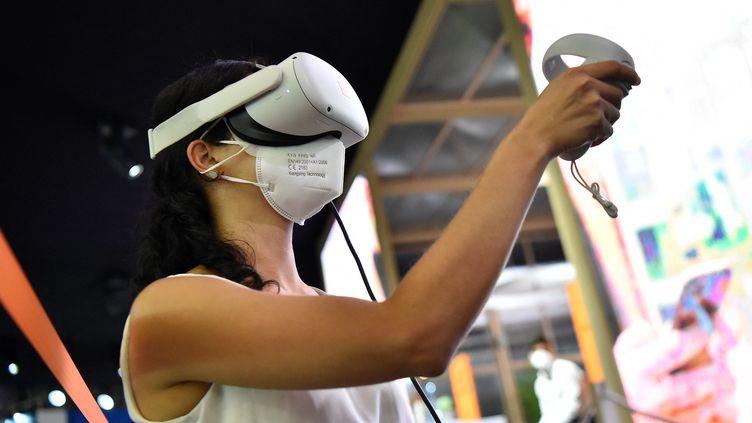 Une femme essaye des lunettes de réalité virtuelle au Mobile world congress de Barcelone, en juin 2021. (PAU BARRENA / AFP)