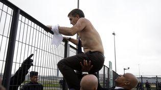 Le directeur des ressources humaines d'Air France, Xavier Broseta, quitte le siège de la compagnie en escaladant une barrière à Roissy (Val-d'Oise), le 5 octobre 2015. (KENZO TRIBOUILLARD / AFP)