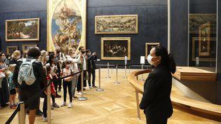 Des visiteurs masqués au musée du Louvre, à Paris, le 6 juillet 2020. (FRANCOIS GUILLOT / AFP)