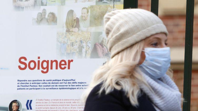 Une femme portant un masque devant l'institut Pasteur à Paris, le 12 mars 2020. (MEHDI TAAMALLAH / NURPHOTO)