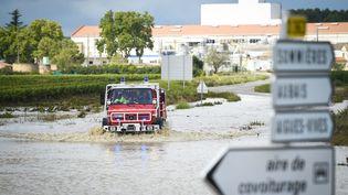 Un camion de pompiers sur une route inondée par les intempéries à Aigues-Vives, dans le Gard, mardi 14 septembre. (SYLVAIN THOMAS / AFP)