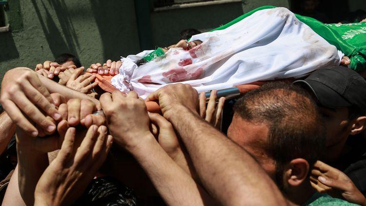 Des Palestiniens portent le corps d'un manifestant tué dans les affrontements avec Israël, le 15 mai 2018, à Gaza. (YANG YUANYUAN / XINHUA)