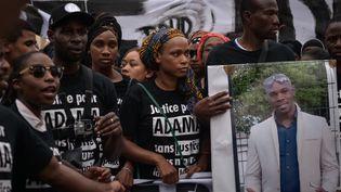 Des manifestants brandissent un portrait d'Adama Traoré, le 30 juillet 2016, à Paris. (JULIEN MATTIA / NURPHOTO)