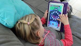 Un enfant joue avec une tablette sur un canapé. (Illustration). (THIERRY GACHON / MAXPPP)
