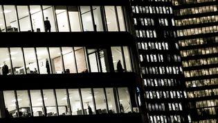 Des personnes travaillant dans les bureaux du quartier d'affaires de la Défense près de Paris (Covid-19), le 2 novembre 2020. Photo d'illustration. (ALAIN JOCARD / AFP)