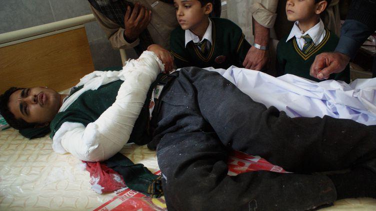 Un étudiant blessé, entouré de deux jeunes élèves, dans un hôpital dePeshawar (Pakistan), le 16 décembre 2014. (A MAJEED / AFP)