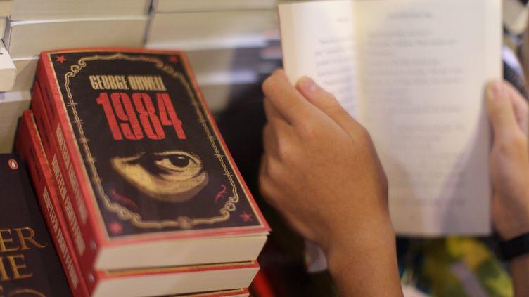 """Un adolescent lit """"1984"""", de George Orwell, lors dusalon du livre de Hong Kong, le 15 juillet 2015. (AARON TAM / AFP)"""