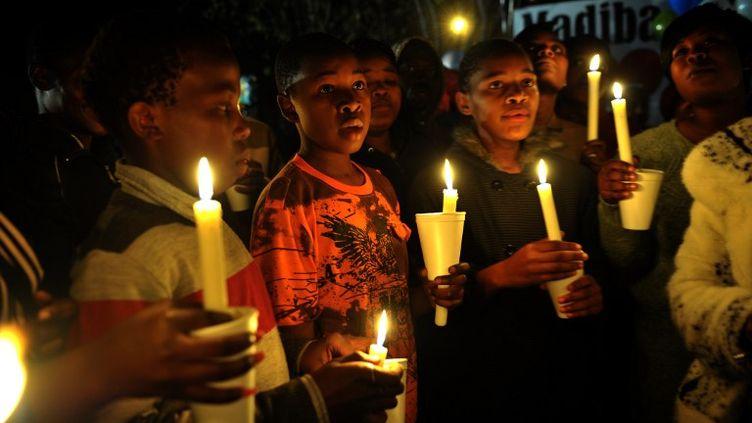 Desanonymes prient, le 26 juin 2013, devant le Mediclinic Heart Hospital de Pretoria (Afrique du Sud),où a été admis Nelson Mandela. (ALEXANDER JOE / AFP)