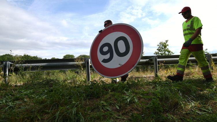 Les employés de la Direction inter-départementale des routes de l'Est remplacent un panneau de limitation à 80km/h, à Wittenheim, le 29 juin 2018. (SEBASTIEN BOZON / AFP)