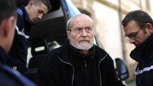 Maurice Agnelet est escorté par des policiers jusqu'au palais de justice de Rennes, le 10 avril 2014, pour son procès pour le meurtre d'Agnès Le Roux. (JEAN-SEBASTIEN EVRARD / AFP)