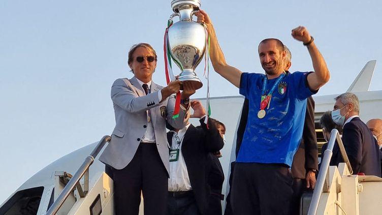 L'entraîneur italien Roberto Mancini et le défenseur Giorgio Chiellini brandissent le trophée Henri-Delaunay à leur arrivée à Rome le 12 juillet 2021 au lendemain de leur victoire en finale face à l'Angleterre. L'Italie vient de remporter son premier titre continental depuis 1968 et ce seulement trois ans après avoir manqué la Coupe du Monde 2018. (AEROPORTO DI ROMA / AFP)