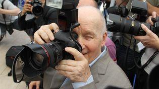 """Facétieux. A 87 ans, l'acteur Michel Bouquet, venu présenter """"Renoir""""préfère jouer les photographes que poser pour eux. (VALERY HACHE / AFP)"""