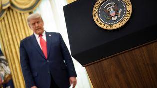 Le président américain, Donald Trump, écoute un discours lors de la remise de la médaille de la Liberté, le 3 décembre 2020 dans le Bureau ovale, à la Maison Blanche (Washington). (BRENDAN SMIALOWSKI / AFP)