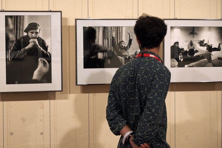 """Un visiteur observe des photographies de Marc Riboud, lors de l'exposition """"Cuba"""", dans le cadre du festival Visa pour l'image, à Perpignan, le 31 août 2016. (RAYMOND ROIG / AFP)"""
