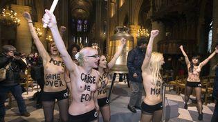 """Huit féministes du mouvement Femen ont manifesté mardi 12 février 2013 dans la nef de Notre-Dame-de-Paris pour """"fêter le départ du pape"""" Benoît XVI. (JOEL SAGET / AFP)"""