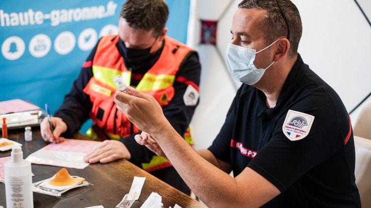 Des pompiers aident à la vaccination à bord d'un vaccibus en Haute-Garonne, le 6 juin 2021. (LILIAN CAZABET / HANS LUCAS / AFP)