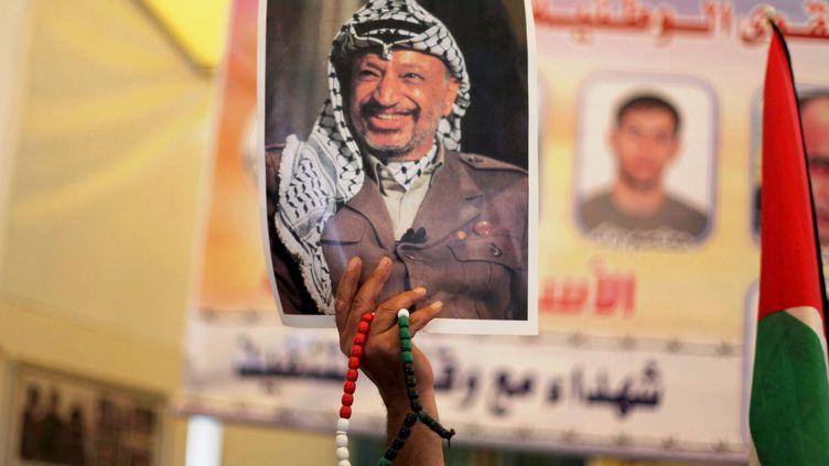 Une photo deYasser Arafat, l'ancien président de l'Autorité palestinienne, brandie par un Palestinien pour commémorer les 10 ans de sa mort, le 10 novembre 2014 à Gaza. (ASHRAF AMRA / ANADOLU AGENCY / AFP)